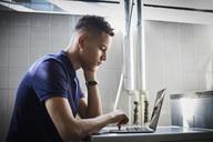 Young university student using laptop while waiting at laundromat - MASF00703