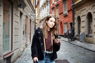 Young woman with mobile phone looking away while standing in alley - MASF00718