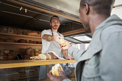 Young salesman giving bottle to male customer at food truck - MASF00730