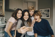 Cheerful friends taking selfie through smart phone while standing at home - MASF00757