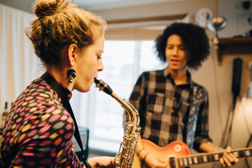 Male and female friends playing saxophone and guitar while practicing at recording studio - MASF00856