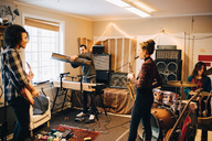 Male and female friends playing various instruments at recording studio - MASF00859
