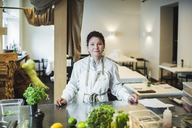 Portrait of confident mature female chef standing at kitchen counter in restaurant - MASF00871