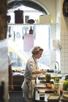 Side view of female chef preparing food on counter in kitchen at restaurant - MASF00886