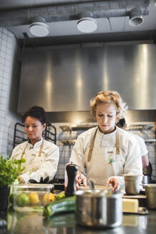 Female chefs preparing food at kitchen counter in restaurant - MASF00895