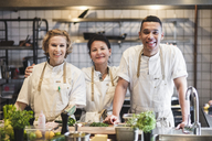 Portrait of smiling confident chefs standing at kitchen in restaurant - MASF00898