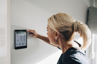 Side view of blond woman adjusting thermostat using digital tablet mounted on white wall at home - MASF00913