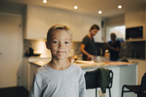 Portrait of boy standing at kitchen with parents in background - MASF00919