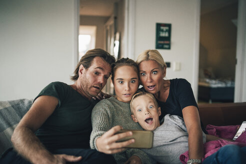 Shocked family taking selfie through smart phone while sitting on sofa at home - MASF00925
