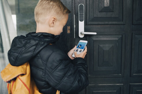 Rear view of boy using app on smart phone to unlock house door - MASF00949
