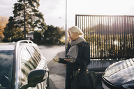 Mature woman standing by car against sky - MASF00955