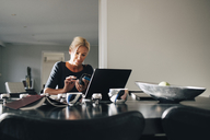 Mature blond woman using smart phone with laptop on dining table at home - MASF00961