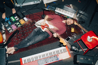 High angle view of man playing guitar while lying on carpet at studio - MASF00982