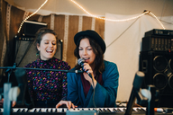 Performers playing piano and singing while practicing in studio - MASF00988