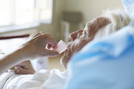 Side view of senior male patient taking cough syrup in hospital ward - MASF01009