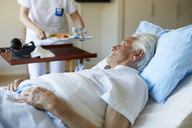 Senior man looking at female nurse serving breakfast while lying on hospital bed - MASF01012