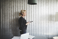 Side view of businesswoman talking on mobile phone against corrugated iron wall at creative office - MASF01024