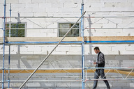 Side view of businessman with blueprint walking at incomplete building on sunny day - MASF01027