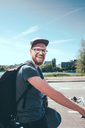 Side view portrait of happy man carrying backpack while riding bicycle on street against sky - MASF01036