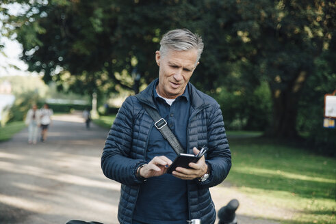Senior man using mobile phone while standing in park - MASF01084