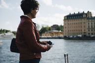 Side view of senior woman holding mobile phone while standing by sea in city - MASF01087