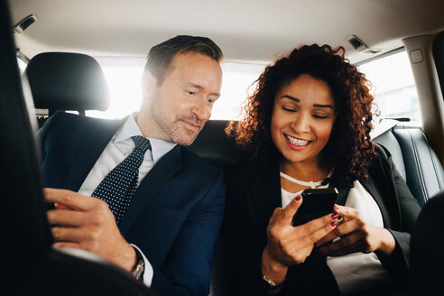 Smiling businessman colleagues sharing smart phone while sitting in taxi - MASF01102