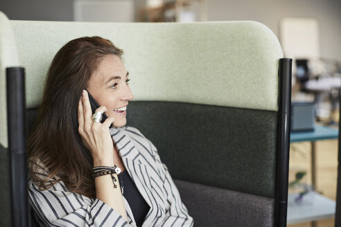 Smiling mature businesswoman talking through mobile phone while sitting on chair at creative office - MASF01129