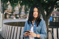 Smiling teenage girl with mobile phone sitting on bench in city - MASF01162