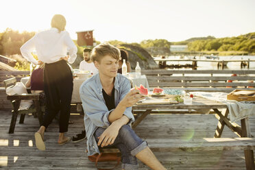 Smiling man eating watermelon slice while friends sitting in background at jetty - MASF01165