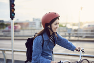 Smiling mid adult woman cycling in city - MASF01177