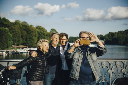 Smiling male and female friends taking selfie with smartphone by railing of bridge - MASF01195