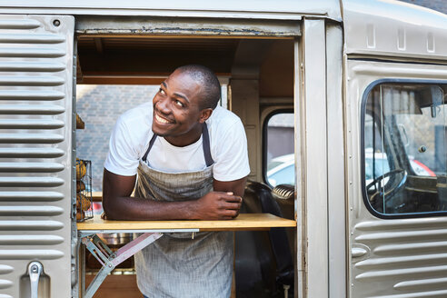 Smiling mid adult male owner looking away while standing in food truck - MASF01243