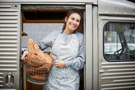 Smiling saleswoman carrying basket of fresh breads in food truck - MASF01246
