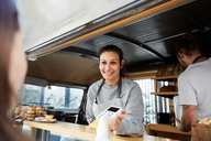 Smiling female owner accepting credit card payment from customer at concession stand - MASF01252