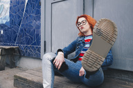 Redhead young woman kicking while sitting against door of building - MASF01269