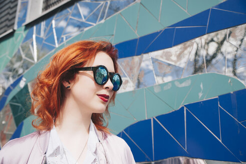Redhead young woman wearing sunglasses against mosaic wall - MASF01272