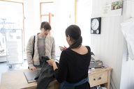 Rear view of mature female Laundromat owner talking with young customer at checkout - MASF01302