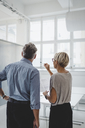 Rear view of mature businessman and businesswoman discussing in new office - MASF01356