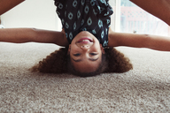Portrait of playful girl doing headstand on rug at home - CAVF35202