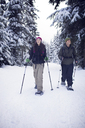 Couple snowshoeing in forest - CAVF35283