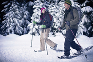 Couple snowshoeing in forest - CAVF35292