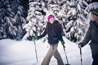 Couple snowshoeing in forest - CAVF35295