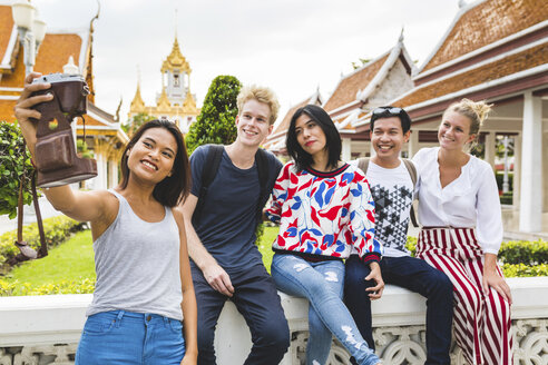 Thailand, Bangkok, five friends taking selfie with smartphone in front of temple complex - WPEF00189