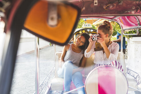 Thailand, Bangkok, two friends riding tuk tuk taking pictures with an old camera - WPEF00192