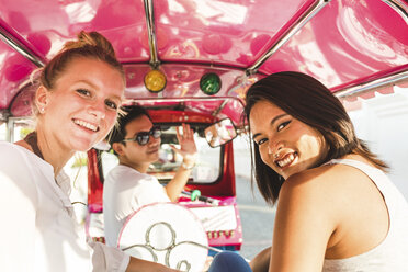 Thailand, Bangkok, portrait of smiling friends riding tuk tuk - WPEF00195
