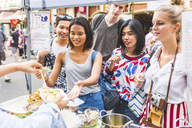 Thailand, Bangkok, Khao San Road, group of friends testing local food on street market - WPEF00201