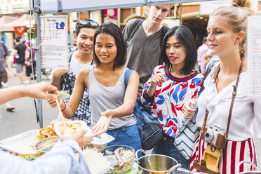 Thailand, Bangkok, Khao San Road, group of friends testing local food on street market - WPEF00201