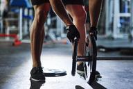 Man preparing barbell in gym - ABIF00239