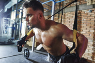 Man doing exercise with suspension straps in gym - ABIF00242