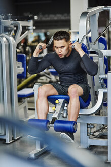 Man training with exercise machine in the gym - ABIF00248